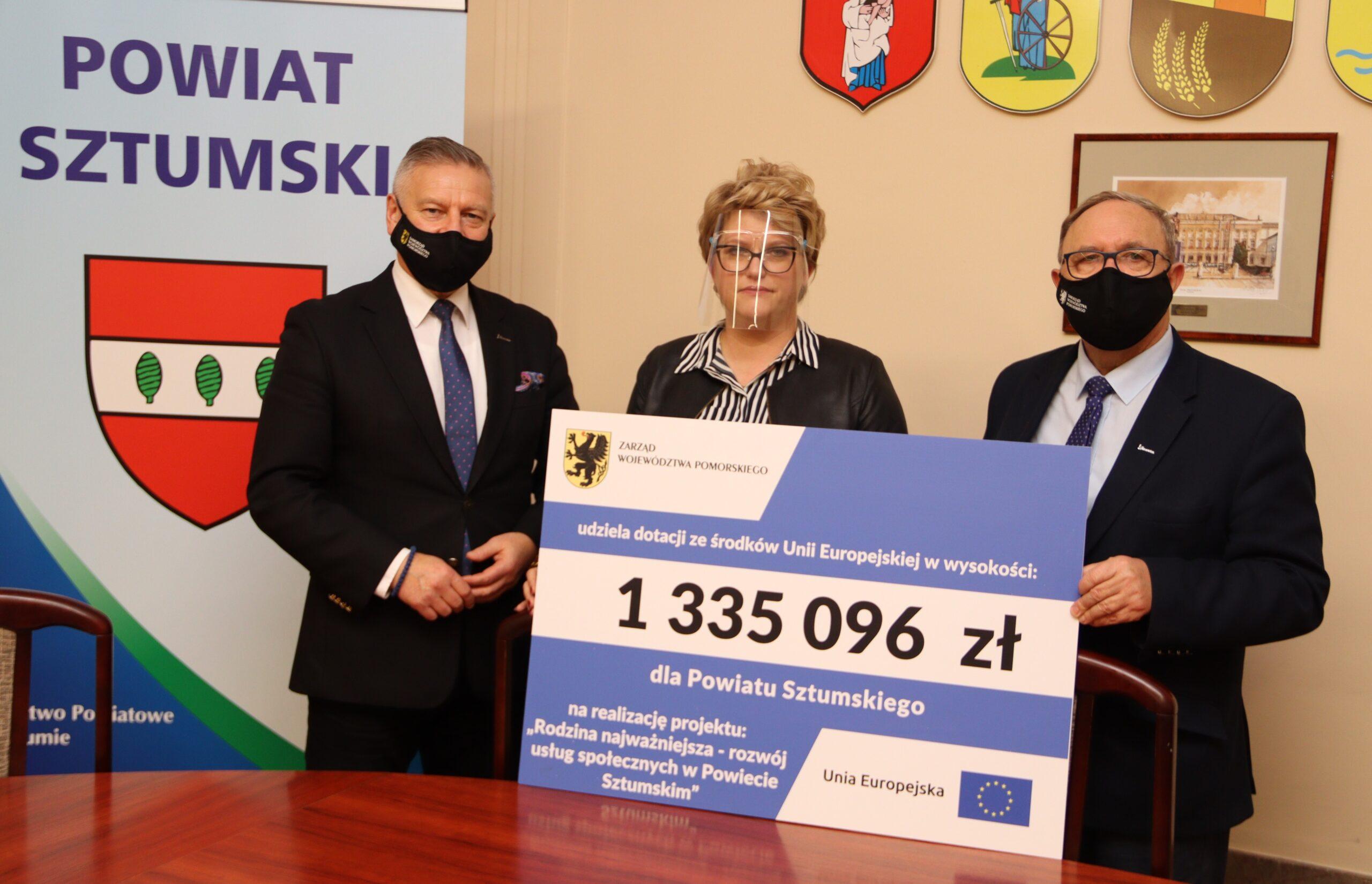 Po prawej stronie Członek Zarządu Województwa Pomorskiego Józef Sarnowski. Po lewej mężczyzna, w środku kobieta. Przedstawiciele powiatu sztumskiego. Wszyscy trzymają symboliczne czek informujący o dofinansowaniu projektu z zakresu usług społecznych